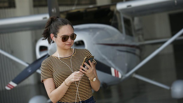 photoshoot of young woman standing near/cleaning an airplane listening to her phone via white Apple ear buds.
