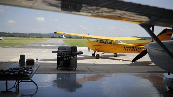 "A staged photoshoot at AOPA's NACC with 15-20 ""flying club members"" interacting in scenarios such as BBQ, flight planning, group watching video, washing airplane, etc."